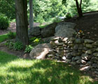 dry stack field stone wall sloped landscape bed